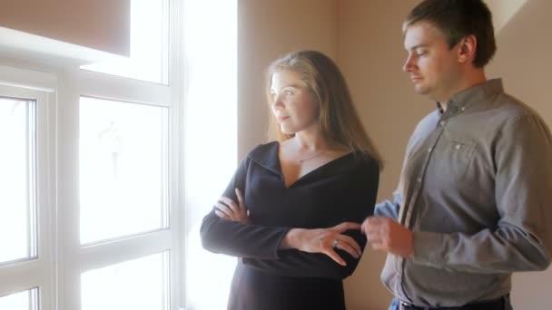 Mladý pohledný muž, objímat a líbat jeho žena, která stojí na velké okno