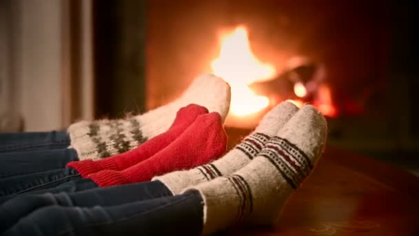 Closeup shot of mother, father and a child in woolen socks warming at the fireplace