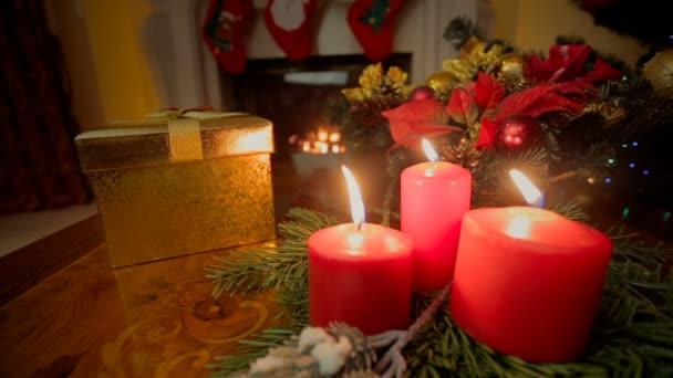 Nahaufnahme von drei brennenden Kerzen und goldener Weihnachtsgeschenkschachtel im Wohnzimmer