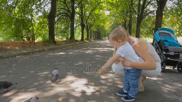 Roztomilý baby boy a mladá matka krmení holuby v parku