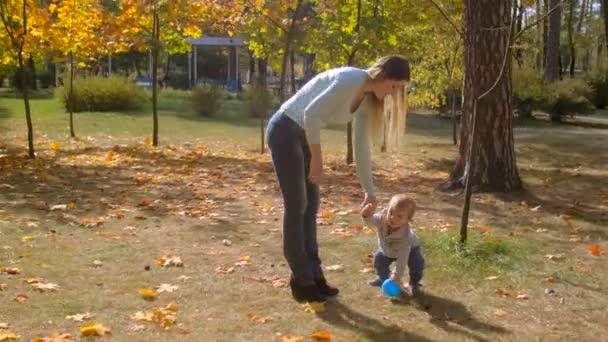 Roztomilé batole chlapec s matky ruku a hrát s míčem na podzim park