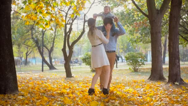 Happy parents playing and kissing their baby son at autumn park