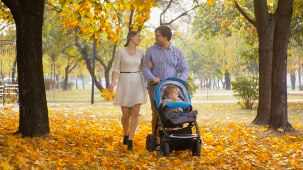 4K footage of happy family with baby in stroller walking at autumn park