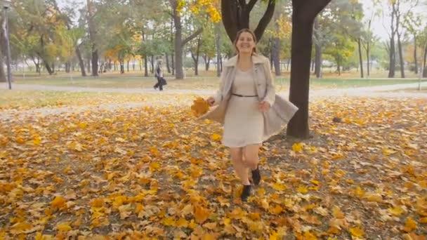 Zeitlupenaufnahmen einer schönen, lachenden Frau, die mit Blättern in der Hand durch den Herbstpark läuft