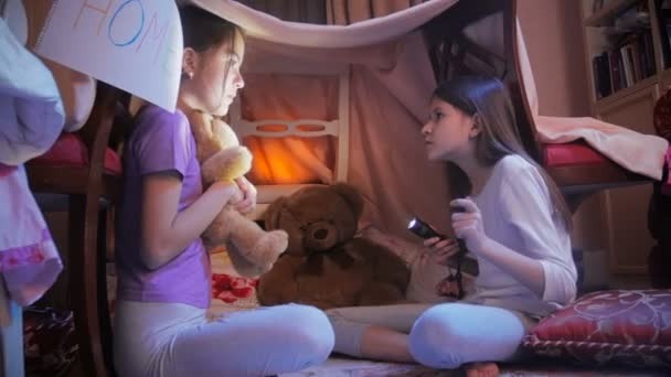 Dvě holky vyprávět strašidelné příběhy ve stanu týpí v ložnici v noci