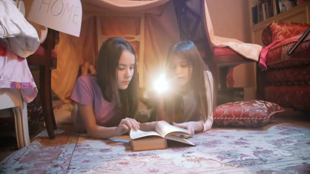 4 k video dvě roztomilé sestry leží na podlaze a čtení knihy s baterkou