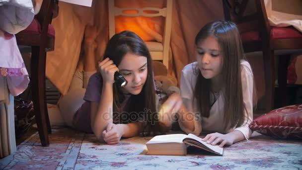Detailní záběr dvou dívek v pyžamu čtení pohádková kniha v ložnici v noci