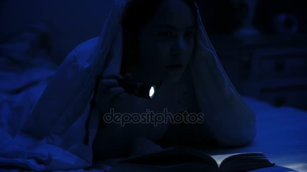 4 k video dívka s baterkou čtení děsivý příběh pod deku v noci