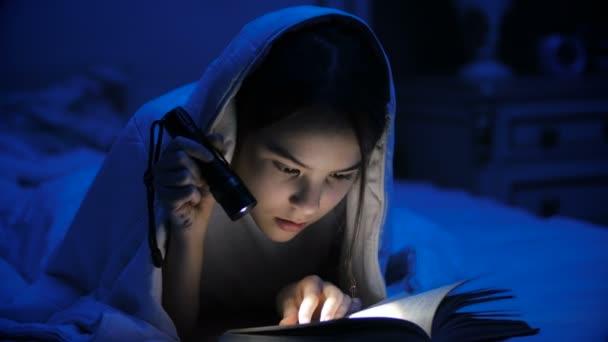 4 k záběry z dospívající dívka čtení děsivé knihy v noci