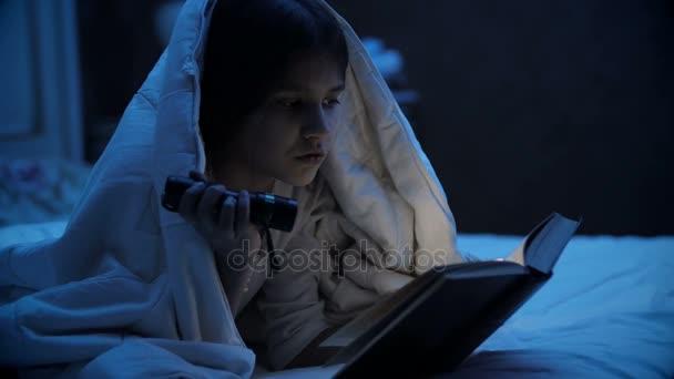 Portrét holčičku čtení knihy horor s baterkou v noci