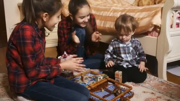 Roztomilý chlapeček hraje s jeho sestrami na koberec v ložnici a stavební věž z bloků