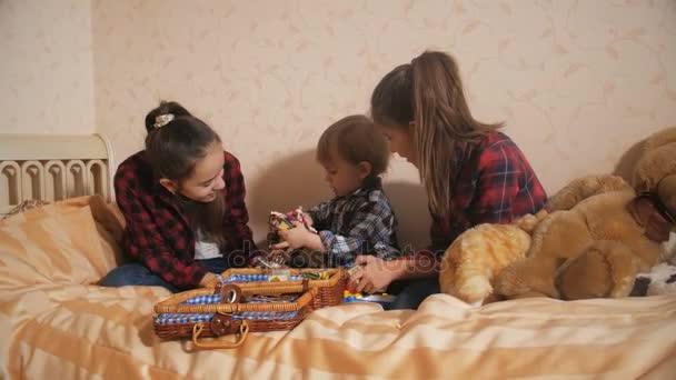 Due sorella maggiore prendersi cura del loro piccolo fratello e giocando sul letto