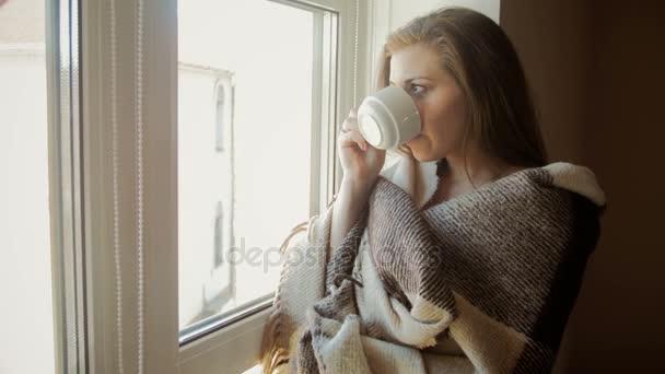 Closeup laděných video mladé ženy v plaid pití kávy na velké okno
