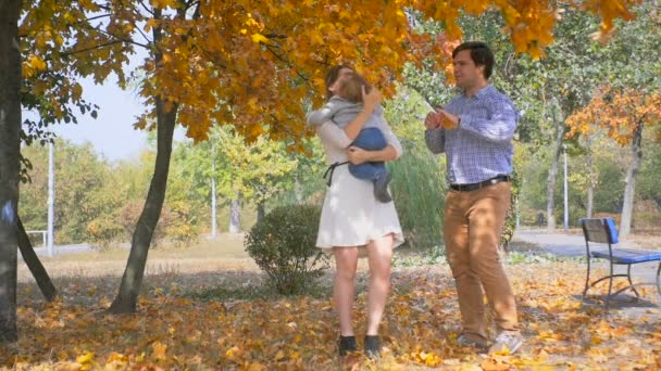Slow motion footage of happy parents having fun with their baby son at autumn park