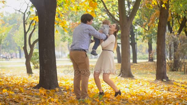 Slow motion of happy young parents hugging their baby son in autumn park at sunny day