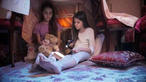 Dolly záběr ze dvou dívek, čtení knihy v stanu týpí v ložnici v noci