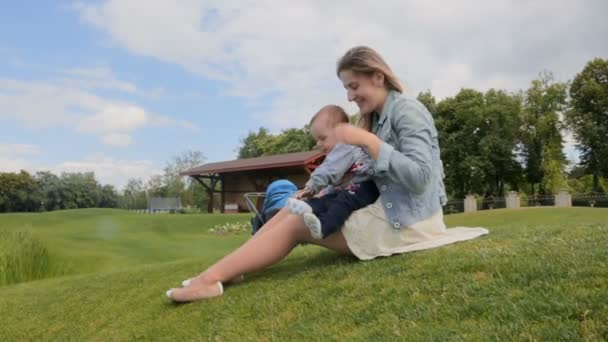 Beautiful young woman sitting on grass at park and cuddling her 1 year old baby son