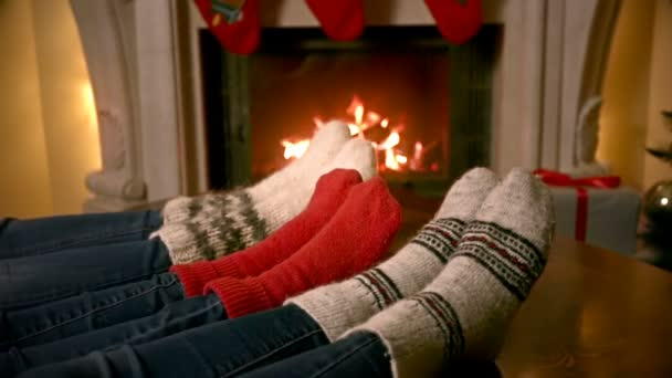 Closeup rodinných stop vlněné ponožky, oteplování krbu, zdobené na Vánoce