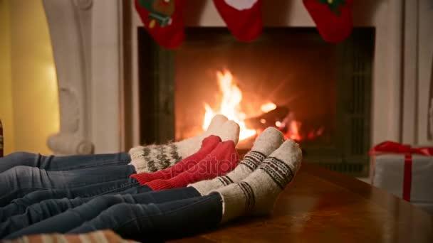 Rodina s dítětem v pletené vlněné ponožky, oteplování na hořící krb v domě