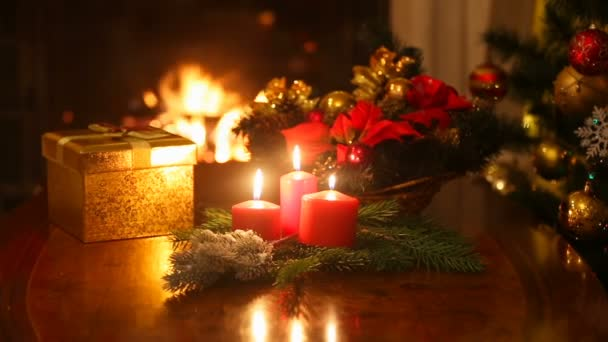 Vánoční dárkové krabice a hořící svíčky před hořící krb v domě