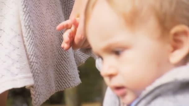 Nahaufnahme Zeitlupenaufnahmen von niedlichen Jungen, die Mütter im Park an der Hand halten