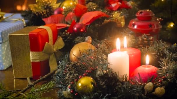 Bella 4k metraggio di tabella decorata di Natale con regali, bagattelle, corona e bruciare candele sul tavolo