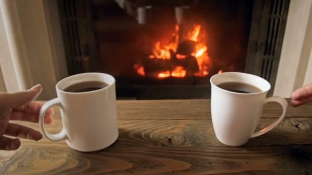 Slow motion záběry z mladého páru s poháry s horkým čajem z dřevěného stolu vedle hořící krb v obývacím pokoji