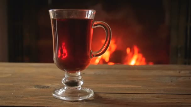 Zpomalený pohyb krb odrážející šálek horkého čaje na dřevěný stůl