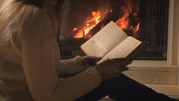 Video se zpomaleným pohybem laděných ženy relaxační s knihou vedle hořící krb v noci
