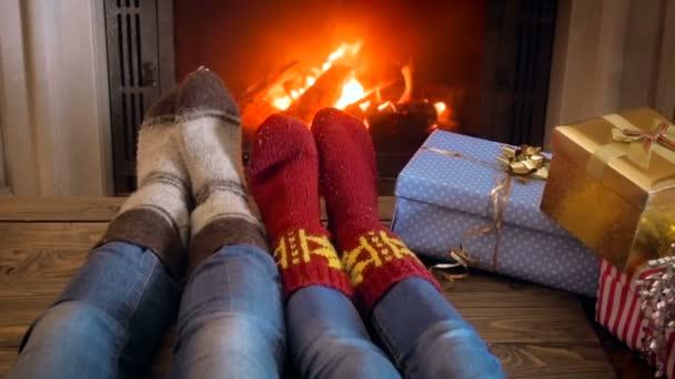 Slow motion záběry z rodiny v vlněné ponožky oteplování nohy u krbu vedle hromadu vánočních dárků