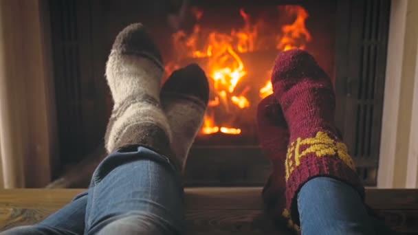 Zpomalený pohyb tónovaný video páru oteplování nohy ve vlněných ponožek v krbu