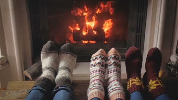 Zpomalené video rodiny s dítětem oteplování nohy ve vlněných ponožek na krb a vánoční stromeček