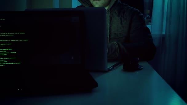 4 k záběry z mladých mužů hacker v hoodie, pracují na notebooku doma v noci. Dokonalé video pro počítačové kriminality