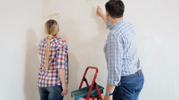4k footage of happy young couple painting walls at their new home