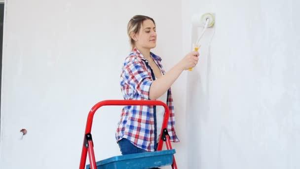 Zeitlupenaufnahmen einer schönen lächelnden Frau beim Bemalen von Wänden mit Farbwalze