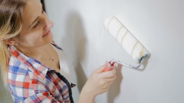 Lassú mozgás felülnézet felvételeket a mosolygó fiatal nő festés fehér fal FESTŐHENGER új ház