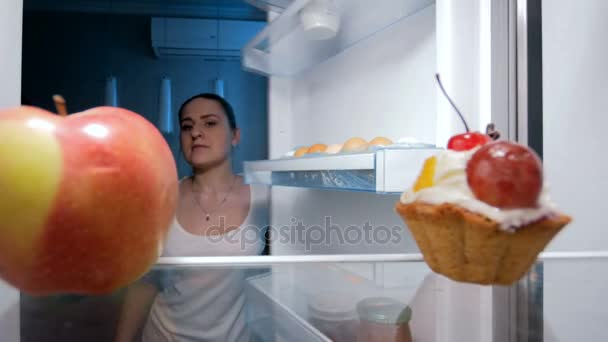 4k footage of young woman taking sweet cake from fridge at kitchen. Concept of unhealthy food and dieting