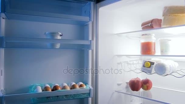 Lassított felvétel nyitott hűtőszekrény a konyha teljes élelmiszer