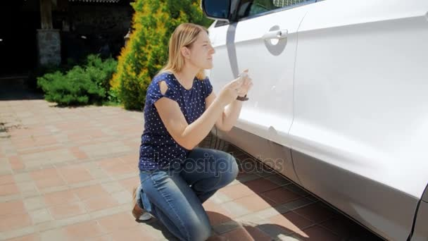 4k video of young woman making photos of her car for insurance company