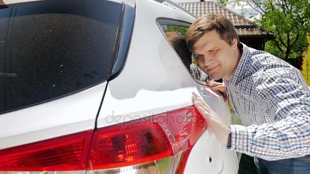 Lassított felvétel, mosolygós fiatalember, finoman megérintette a kocsija