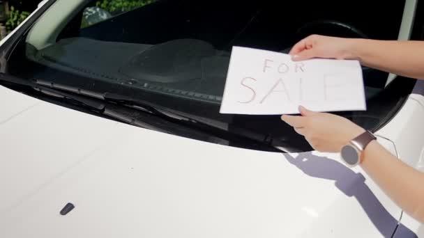Slow motion záběry mladé ženy dávat na prodej znamení na její automobily čelního skla pod stírači