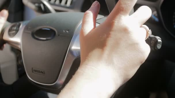 Closeup slow motion footage of female drivers hands on car steering wheel