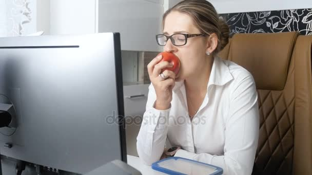 4k video of elegant businesswoman eating red apple in offce during lunch break
