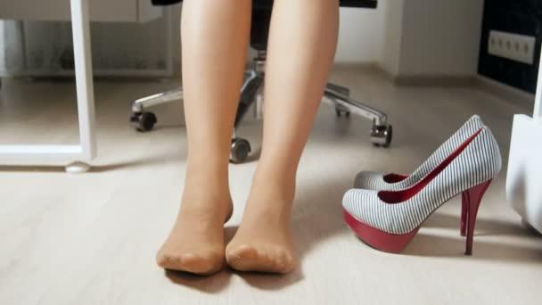 4 k video-ból szexi üzletasszony lábak pihenés után magas sarkú cipőben irodában