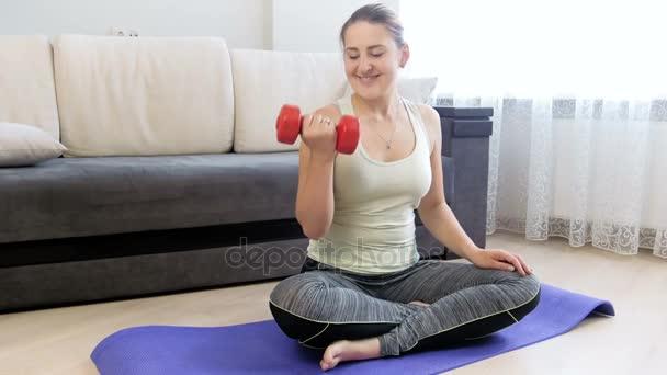 4 k záběry z mladé ženy zvedání červené dumbbels při cvičení doma