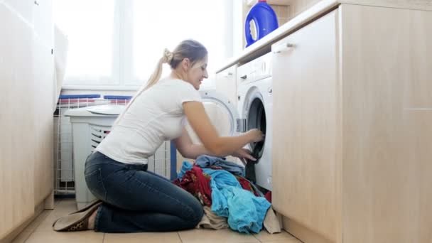 4 k Video junge Hausfrau setzen großen Haufen schmutzige Wäsche in der Waschmaschine