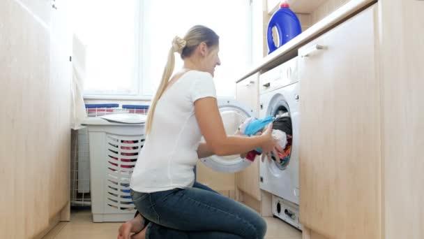 4k-Video der schönen jungen Frau, die saubere Kleidung aus der Waschmaschine im Badezimmer holt