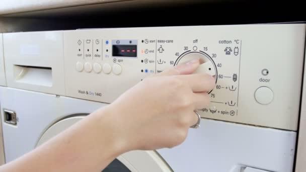 4k Nahaufnahme einer jungen Frau bei der Wahl von Temperatur und Programm in der Waschmaschine an der Wäscherei