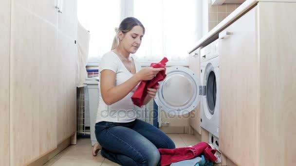 4 k Video junge Hausfrau schmutzigen Stunky Socken riechen und wirft es in Waschmaschine