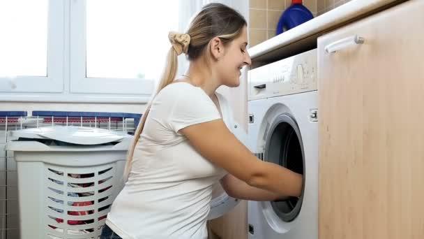 Zeitlupenaufnahmen einer fröhlichen jungen Frau, die große Kleiderberge in die Luft wirft, um Wäsche zu waschen